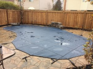 A backyard swimming pool that has had a winter safety cover installed