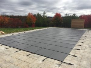 A swimming pool with a safety cover installed to prepare it for winter