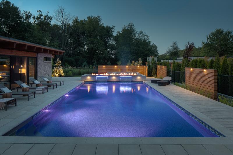 Nighttime image of custom backyard swimming pool