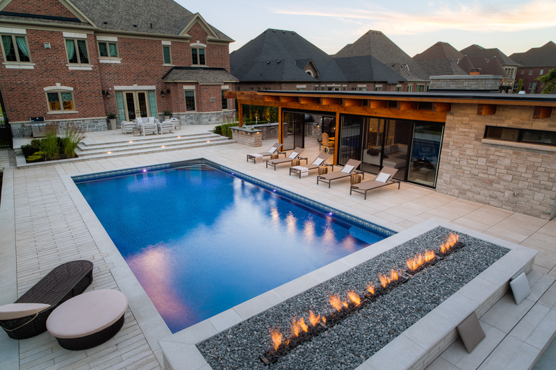 A vinyl swimming pool with outdoor firepit feature