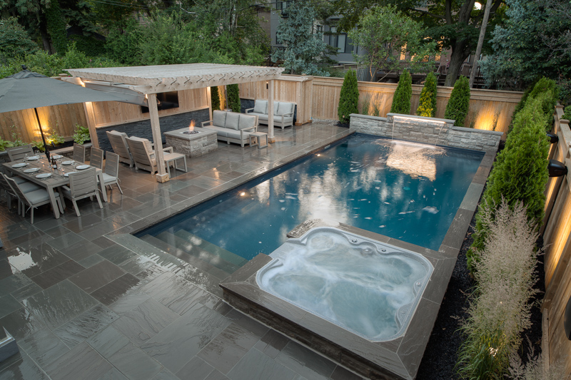 A backyard swimming pool with attached spill over spa