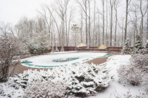 Snowy backyard with white bushes and snow covered swimming pool in late March during an unexpected snowfall