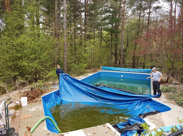 A team folding and putting away a swimming pool cover
