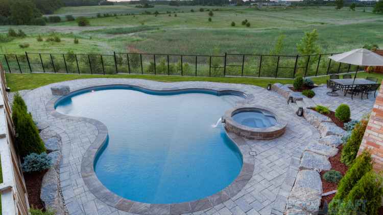 custom shape pool with spill over spa