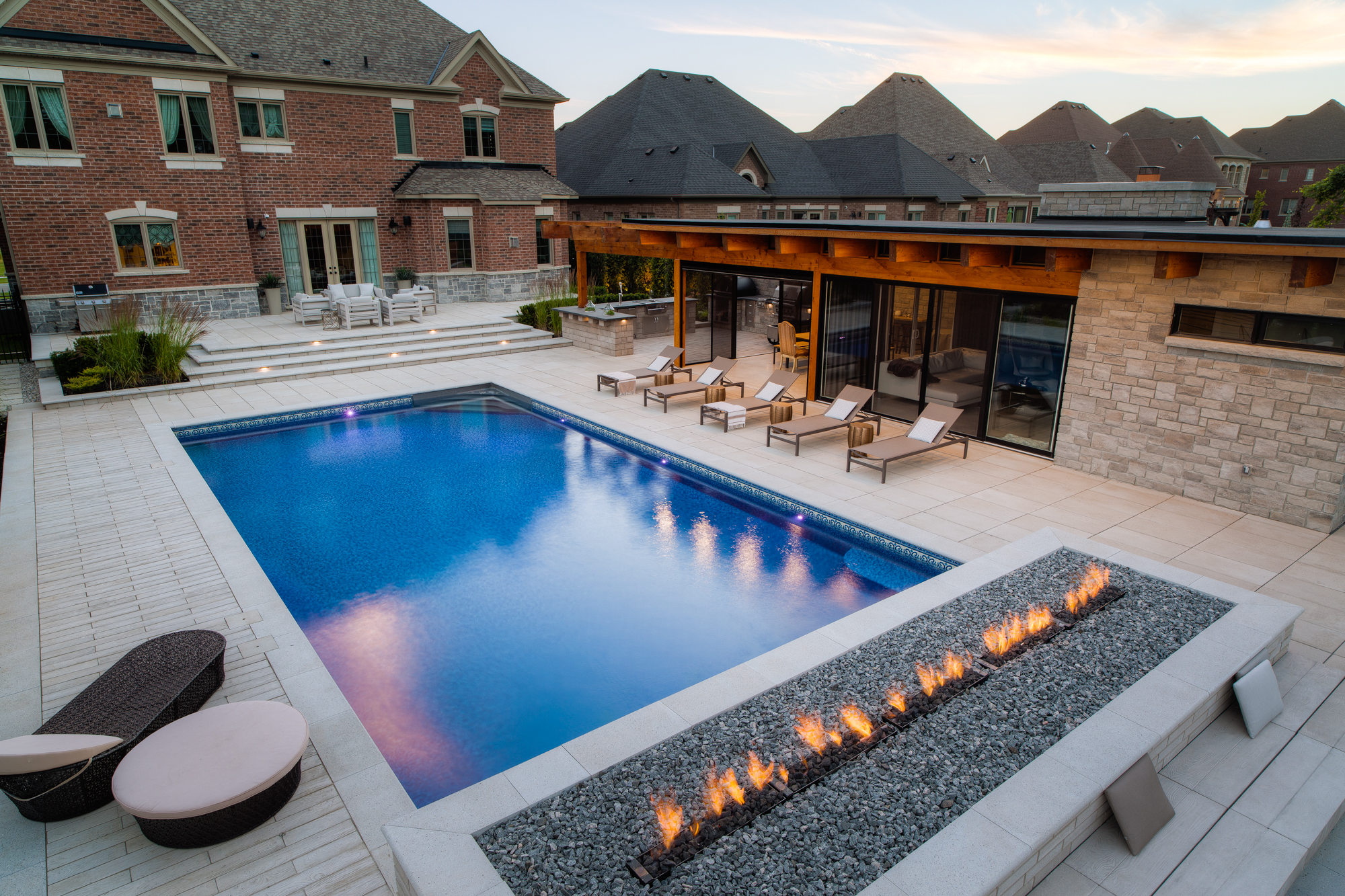 A backyard pool and patio with outdoor fireplace and furniture