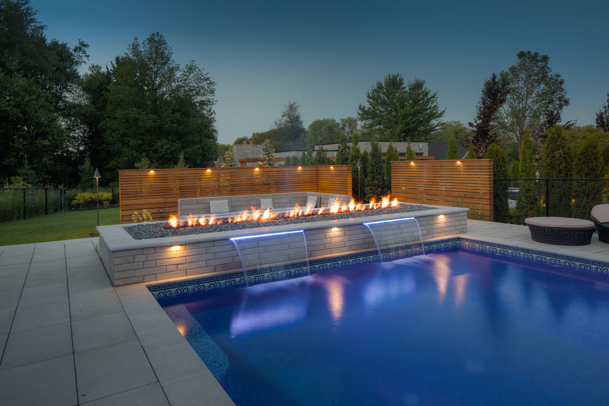A cascade water features with an outdoor firepit, installed by Swimming Pool Company Pool Craft