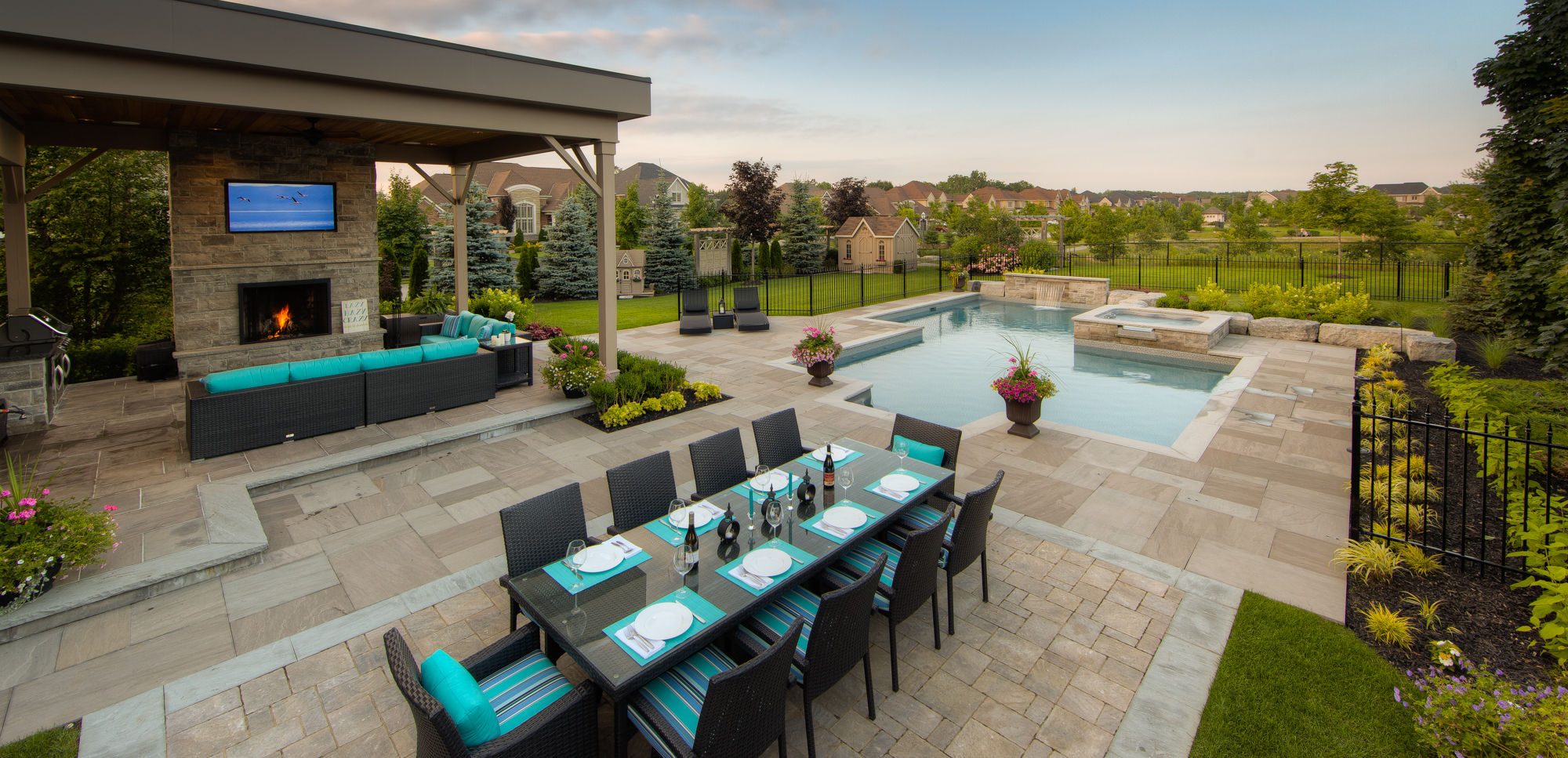 A residential swimming pool and patio with outdoor furniture