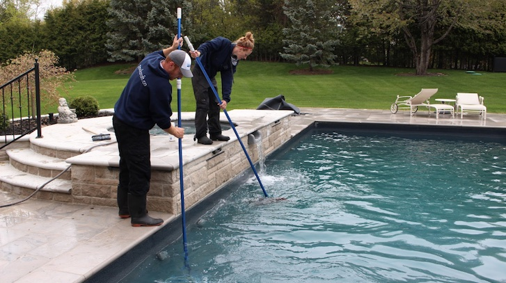 The expert team at Pool Craft cleaning a swimming pool during spring