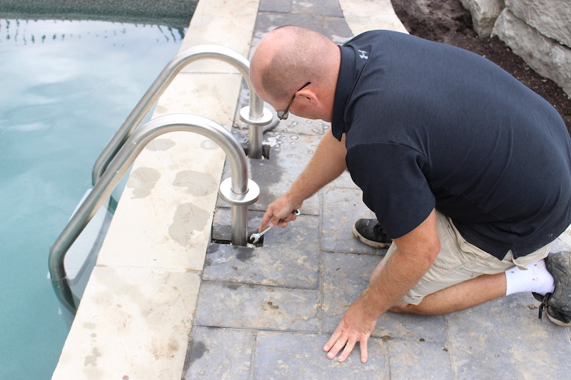 A pool contractor inspects equipment in a swimming pool