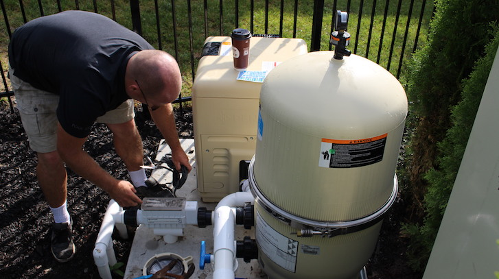 A man updates swimming pool equipment and also inspects and makes fixes
